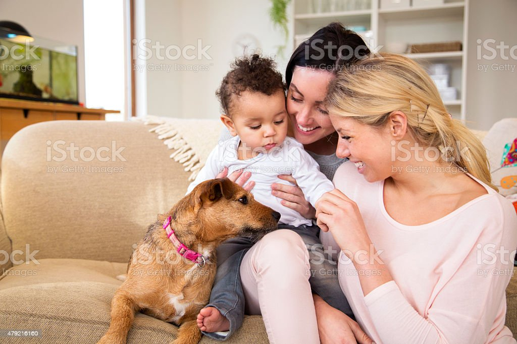 Female couple with son and dog at home stock photo