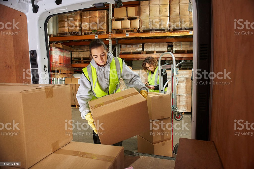 female courier filling her van stock photo
