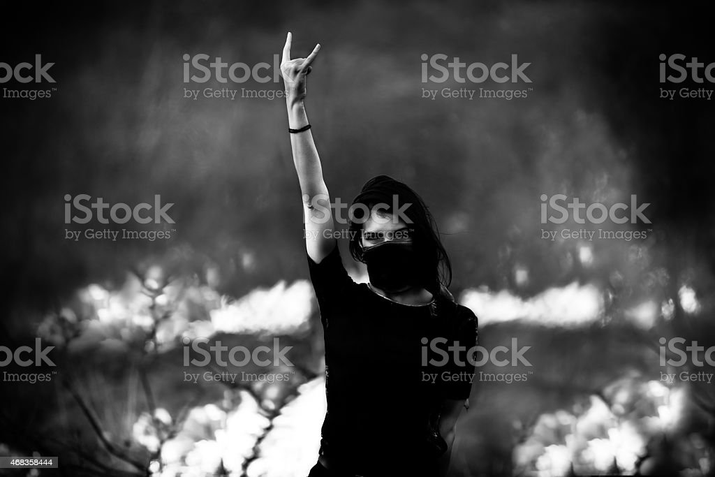 Female covering face with bandana representing anarchy stock photo