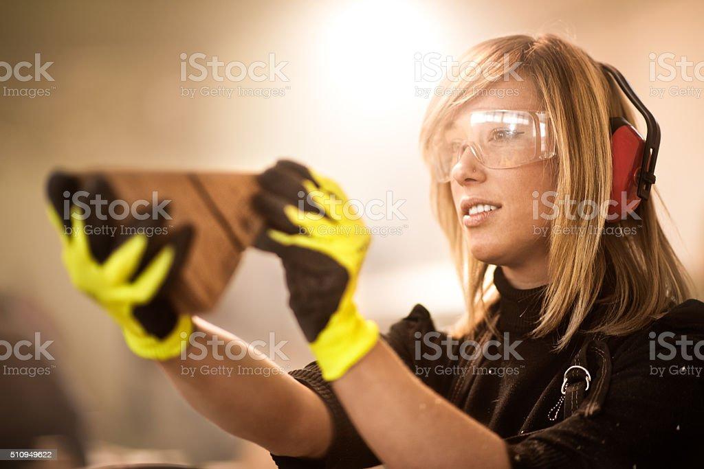 Female craftsperson holding piece of wood stock photo