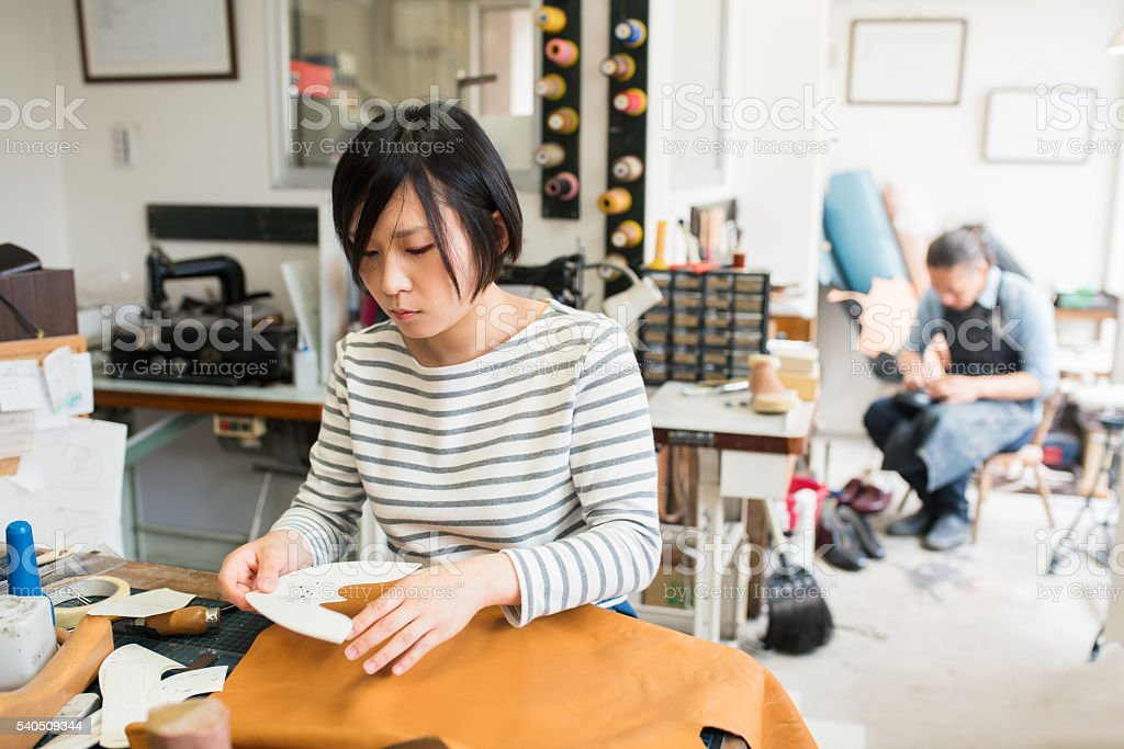 Female craftsperson making a pair of shoes stock photo