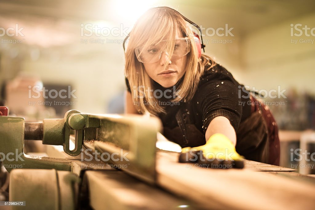Female craftsperson working with plank stock photo
