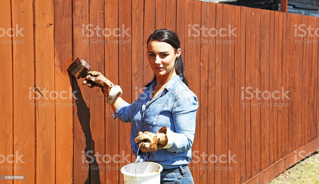 female creosoting her fence stock photo