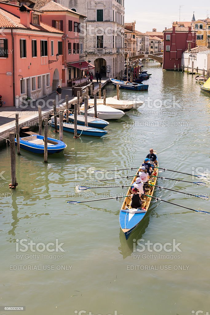 Female crew is training on a rowing boat in Venice. stock photo