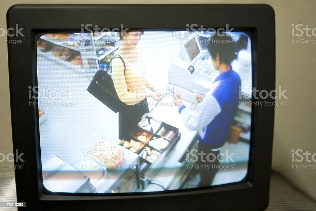 Female customer and salesclerk of convenience store onsecurity camera stock photo