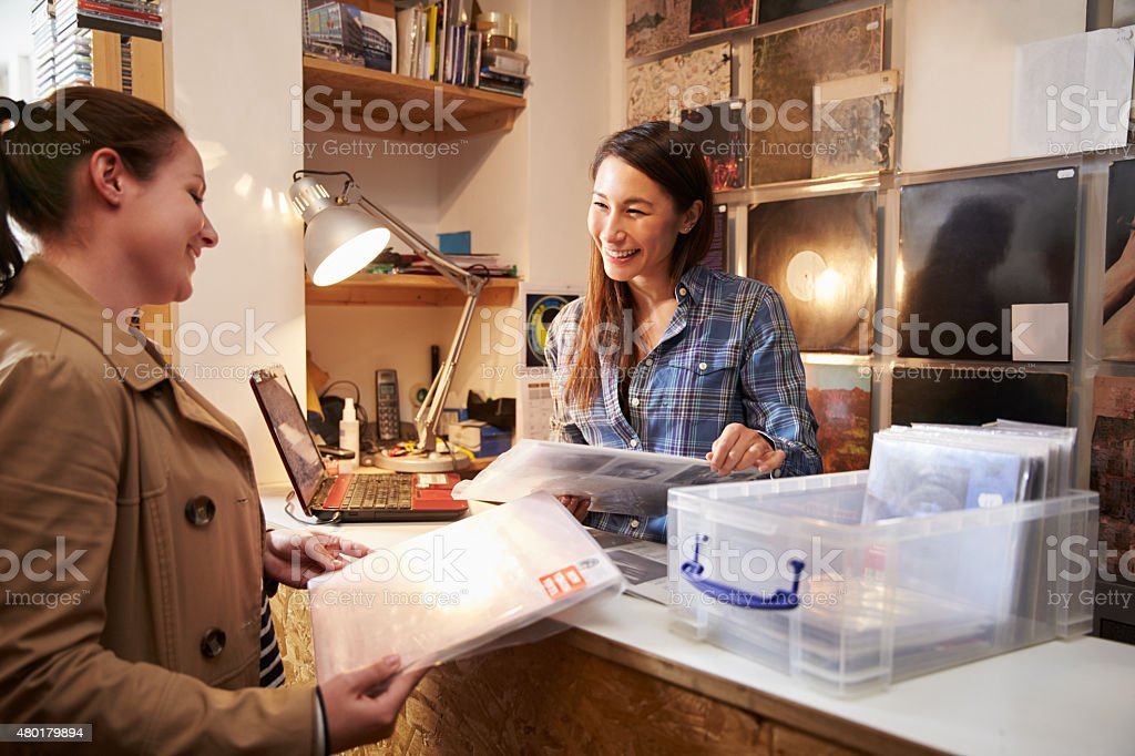 Female customer being served at counter of a record shop stock photo