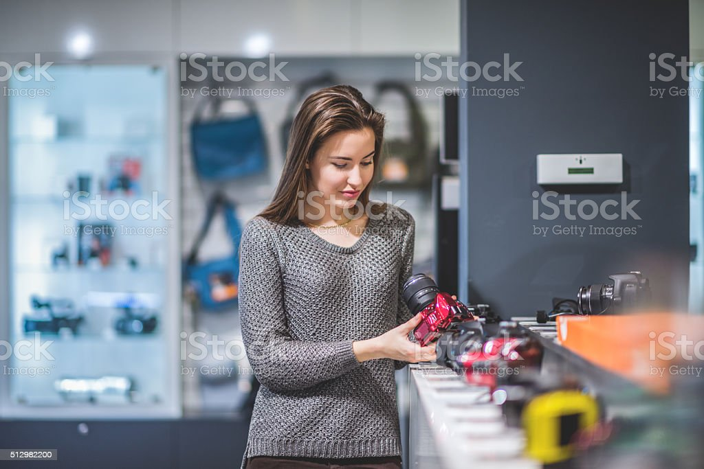 Female customer choosing digital camera stock photo