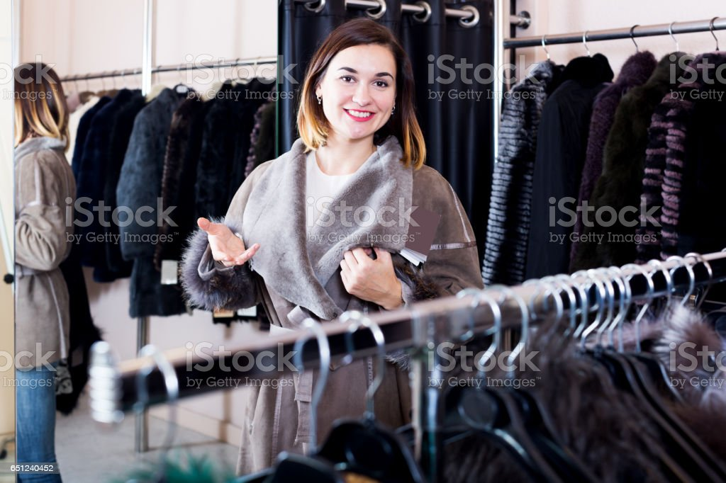 Female customer examining new sheepskin coat stock photo