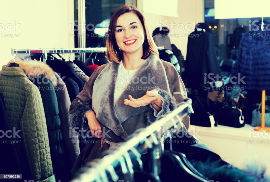 Female customer examining new sheepskin coat stock photo