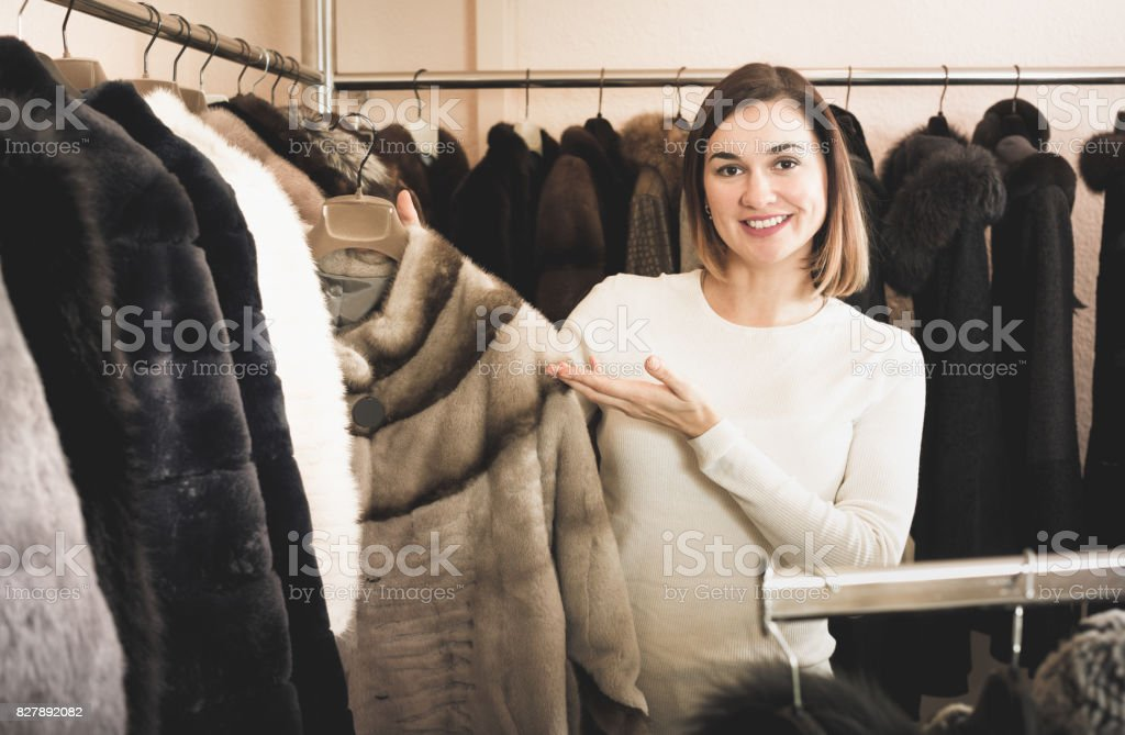 Female customer examining short coffee-colored fur jacket stock photo
