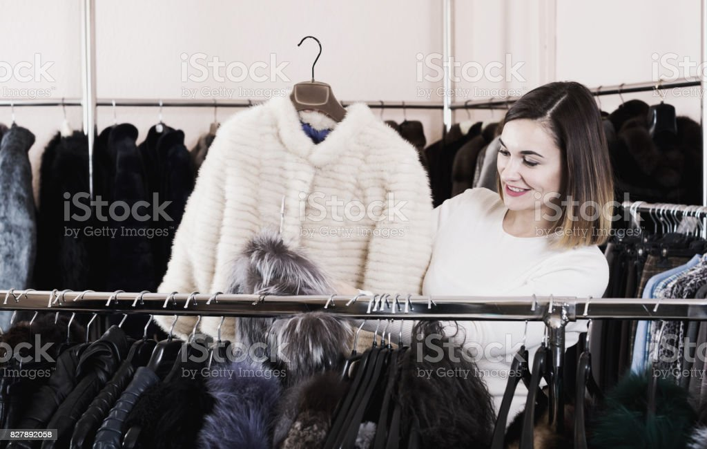 Female customer examining white mink jacket stock photo