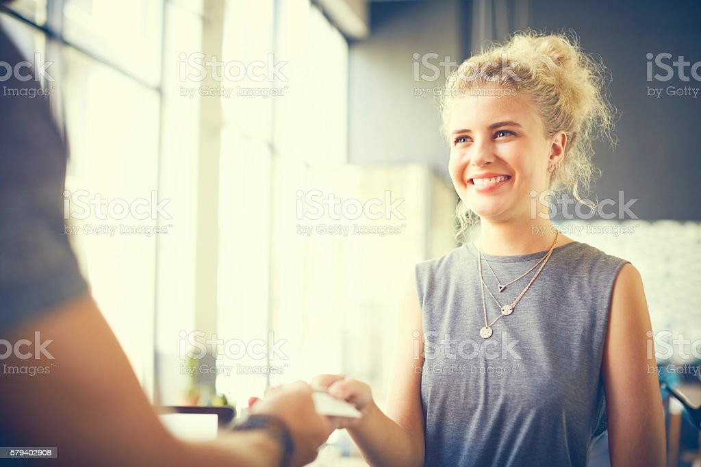 Female customer giving card to cashier in cafe stock photo