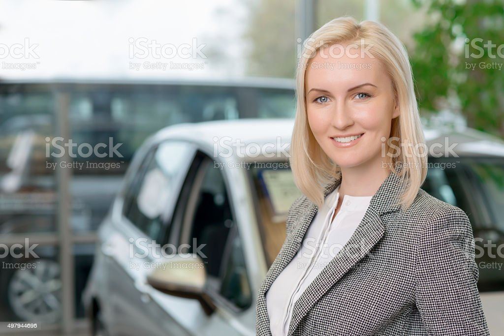 Female customer is standing in front of a car stock photo