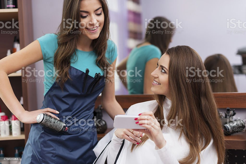 Female customer showing which hairstyle she wants on mobile phone stock photo