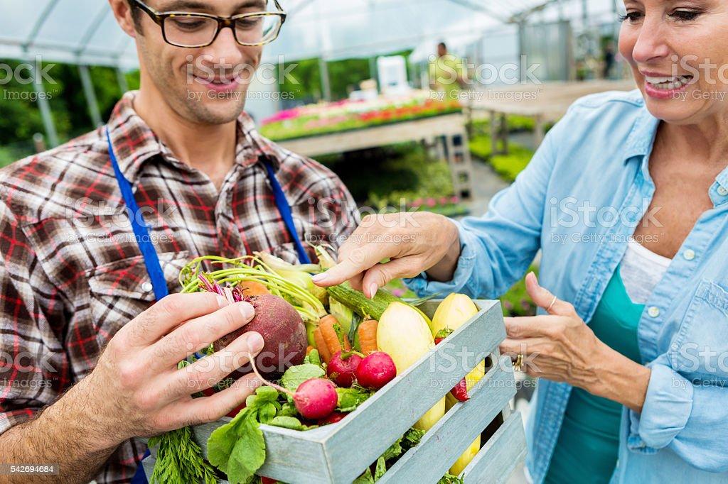Female customer talks with farmer about organic produce stock photo