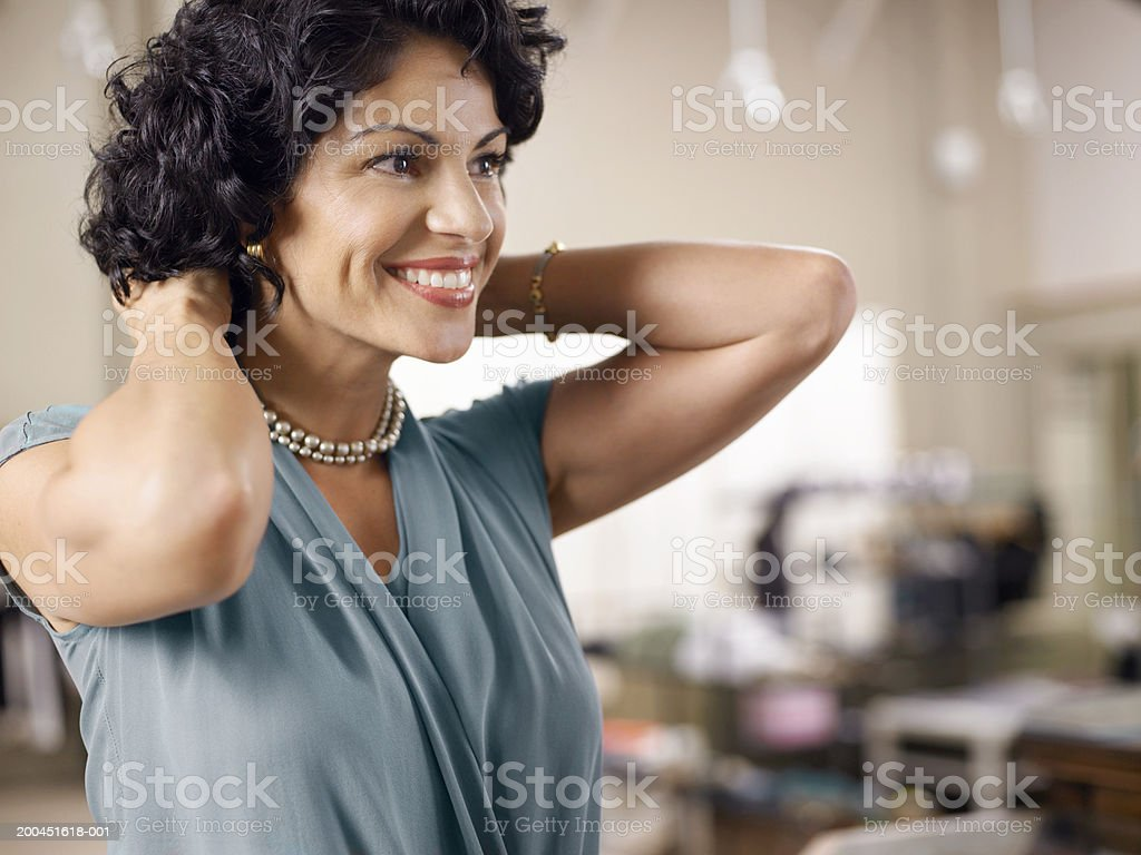 Female customer trying on pearl necklace in shop stock photo