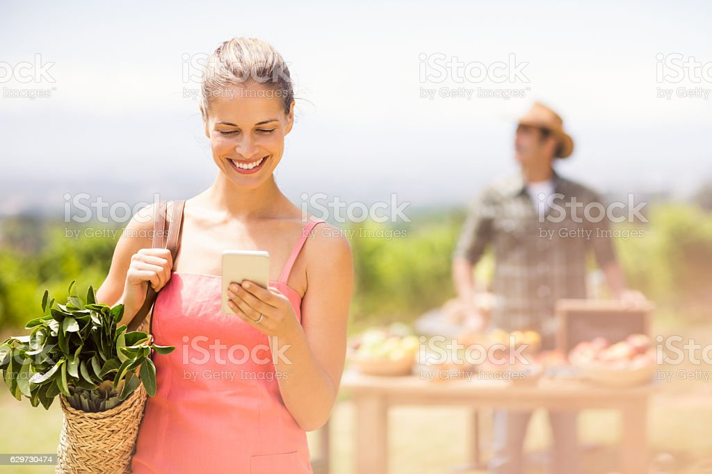 Female customer using mobile phone in front of vegetable stall stock photo