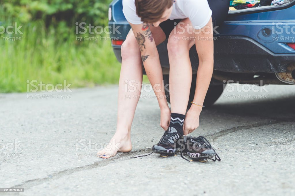 Female cyclist puts on her cycling shoes stock photo