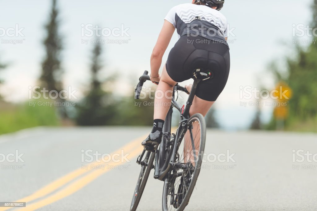 Female cyclist rides along a rural highway stock photo