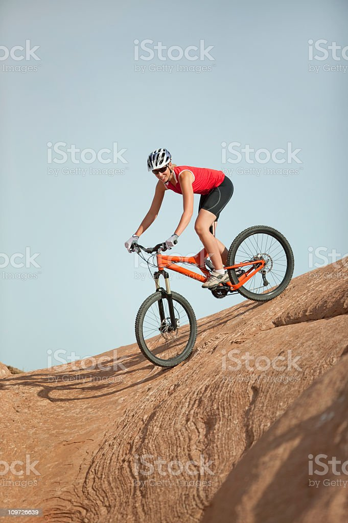Female Cyclist Riding Downhill On Slickrock Trail In Moab, Utah royalty-free stock photo