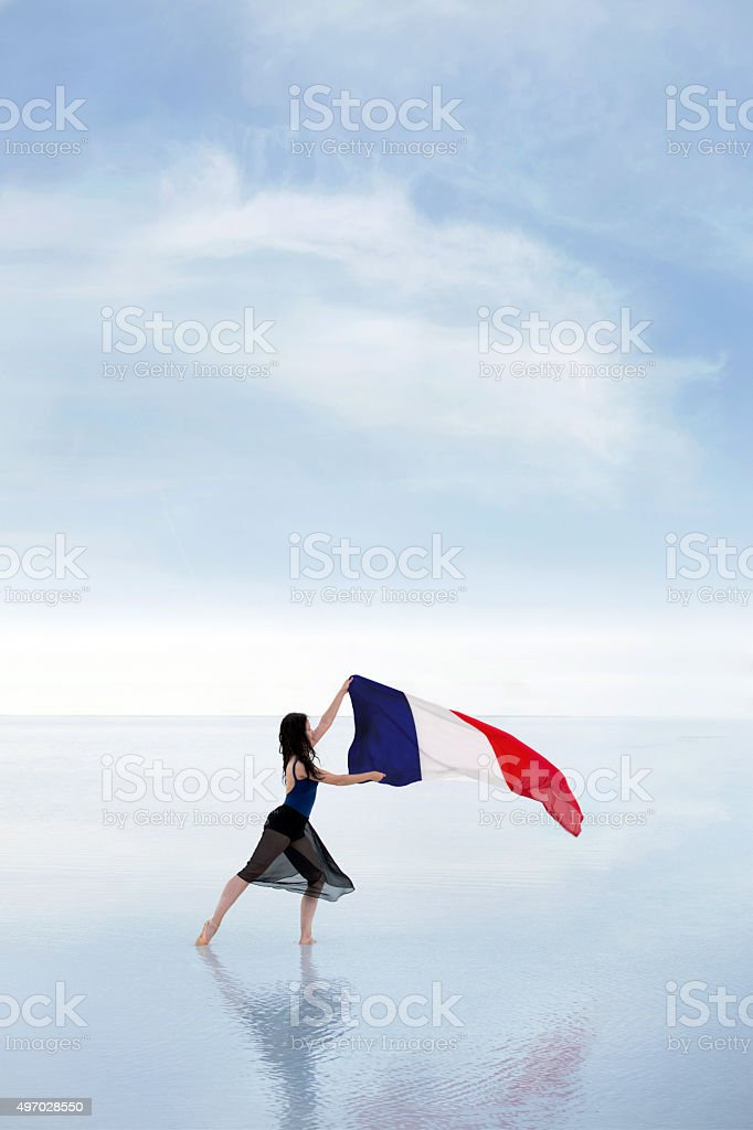 Female dancer carrying French flag waving in the wind outdoors stock photo