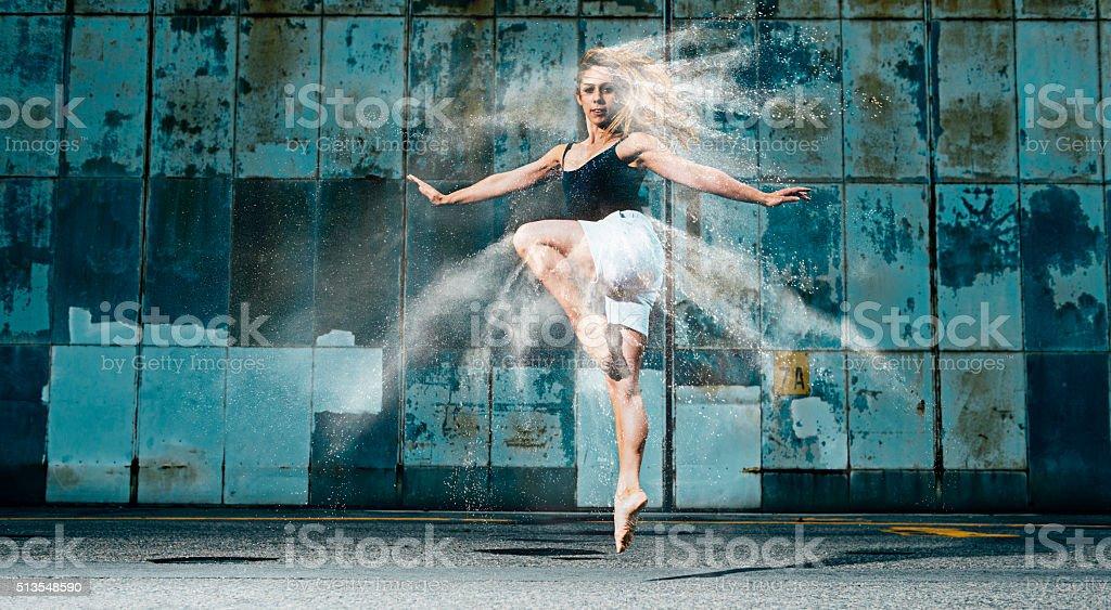 Female dancer jumps through a cloud of flour stock photo