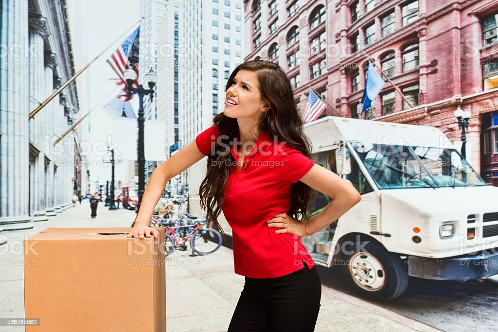 Female delivery person feeling back pain outdoors stock photo