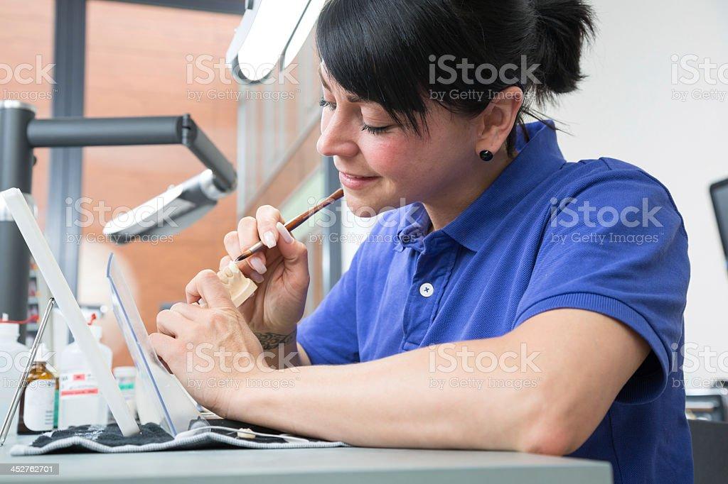 Female dental technician applying ceramics to a prosthesis stock photo