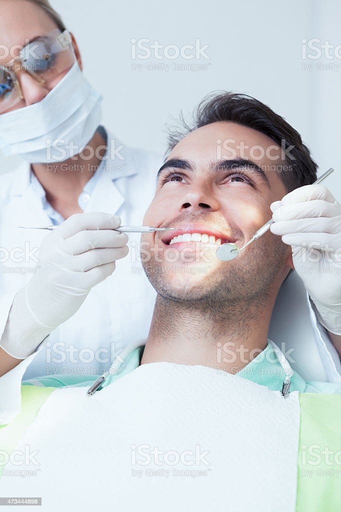 Female dentist examining mans teeth stock photo
