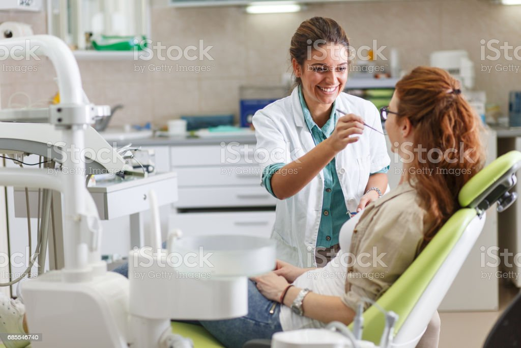 Female dentist in dental office talking with female patient stock photo