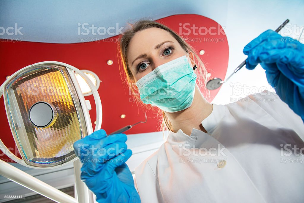 Female dentist in surgical mask holding dental tools. stock photo
