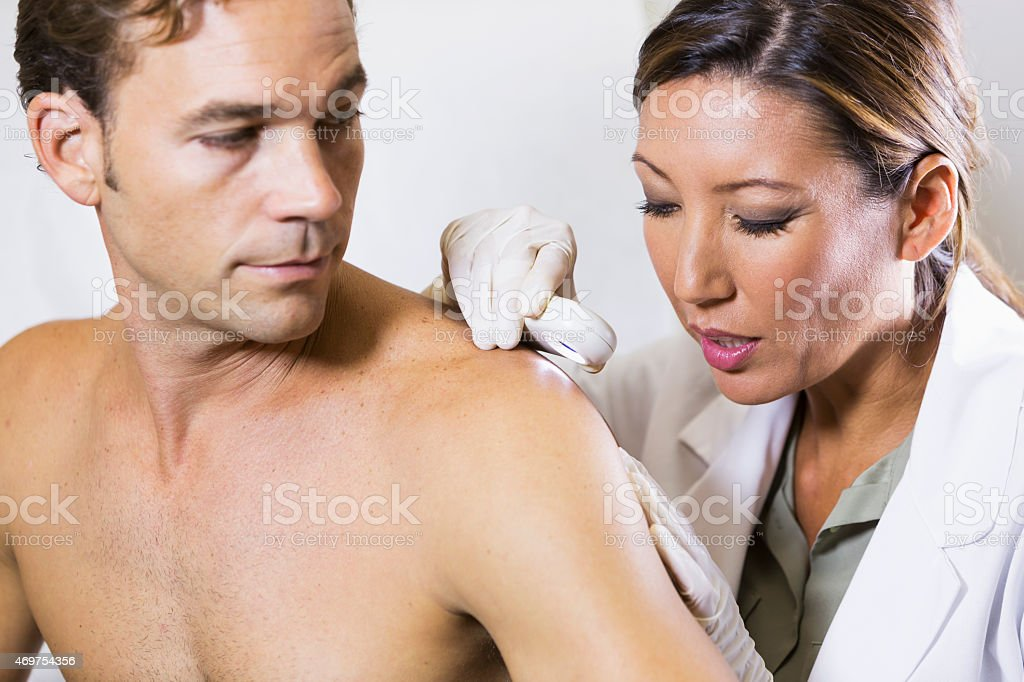Female dermatologist examining a male patient stock photo