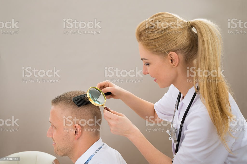 Female Dermatologist Looking Hair Through Magnifying Glass stock photo