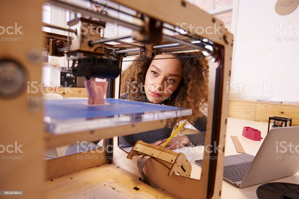 Female Designer Working With 3D Printer In Design Studio stock photo