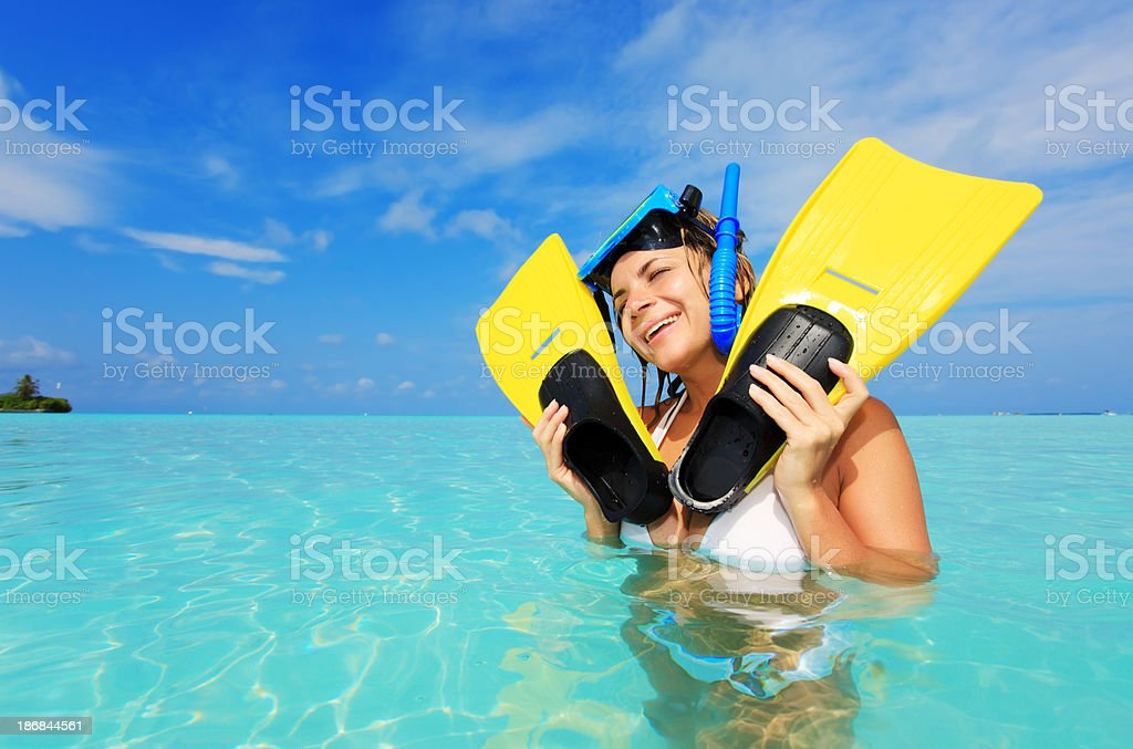 Female diver at the sea holding flippers in  hands. stock photo