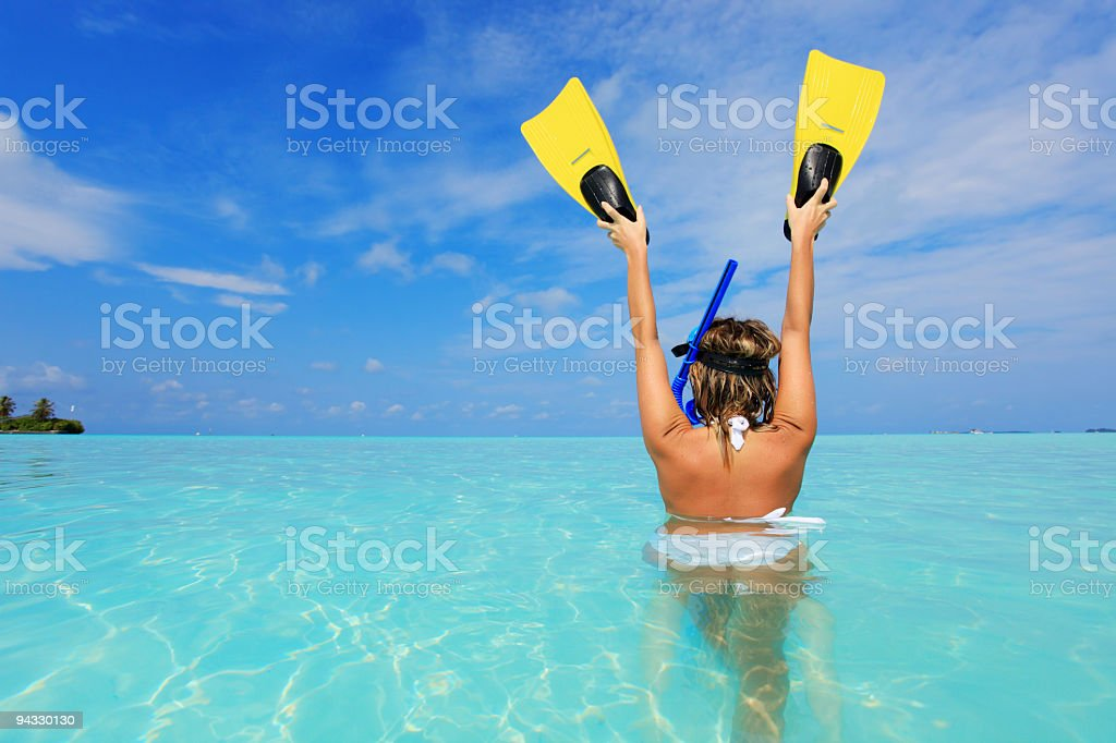 Female diver at the sea holding flippers in raised hands stock photo