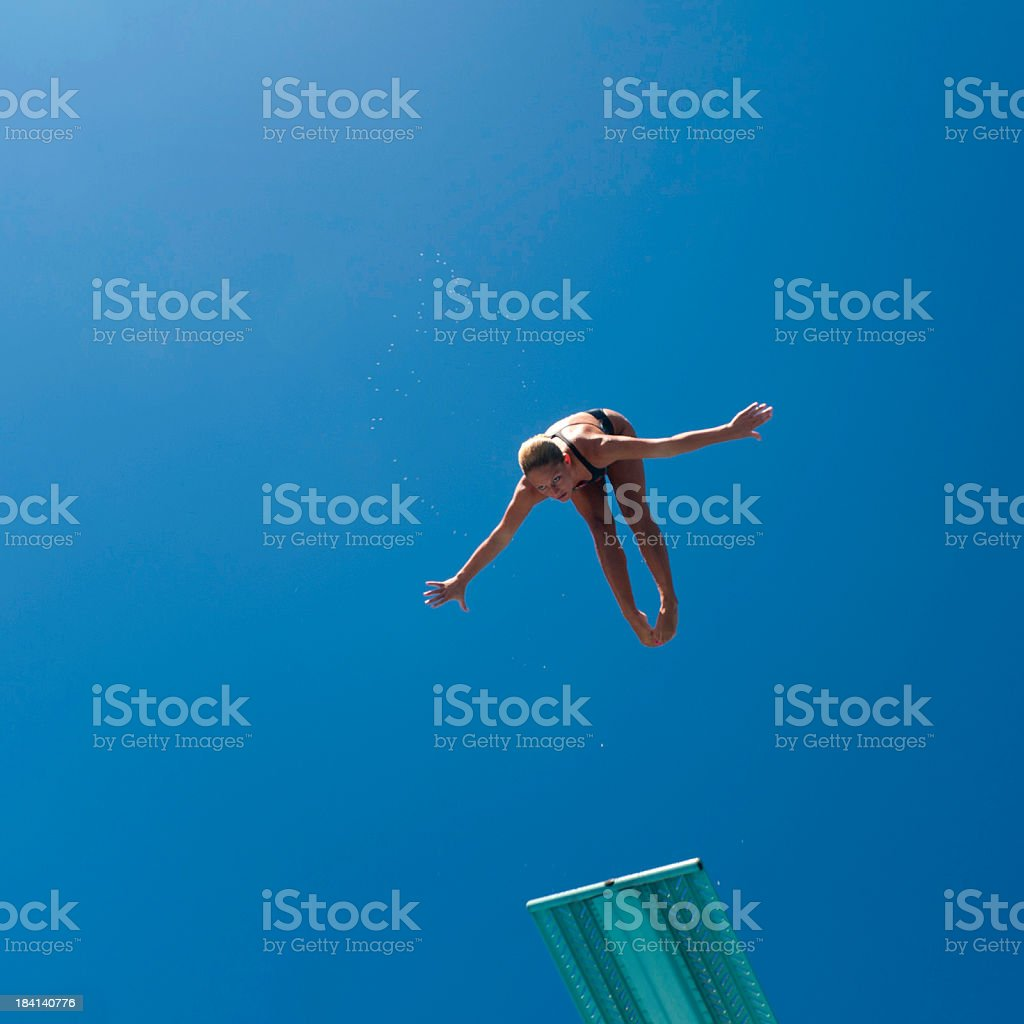 Female diver in the air with a blue sky behind her stock photo