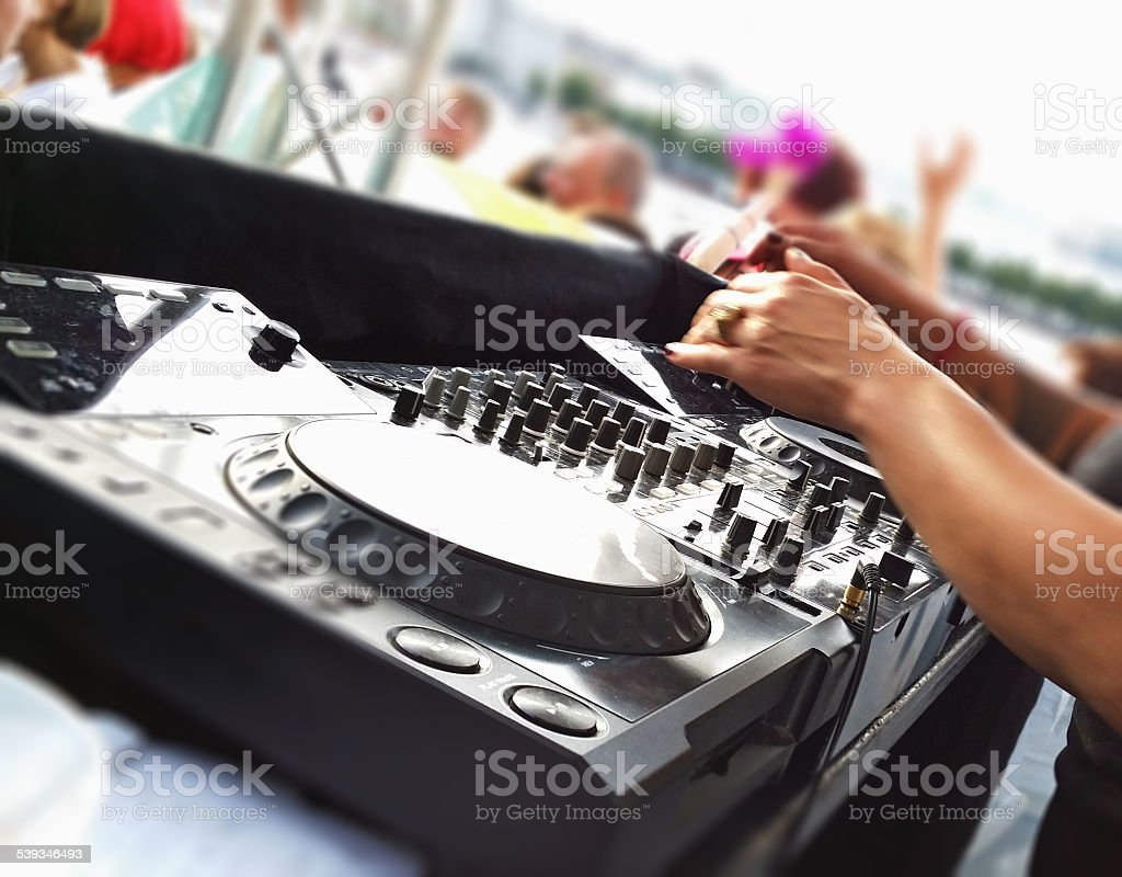 Female Dj mixes dance tracks at open air party stock photo