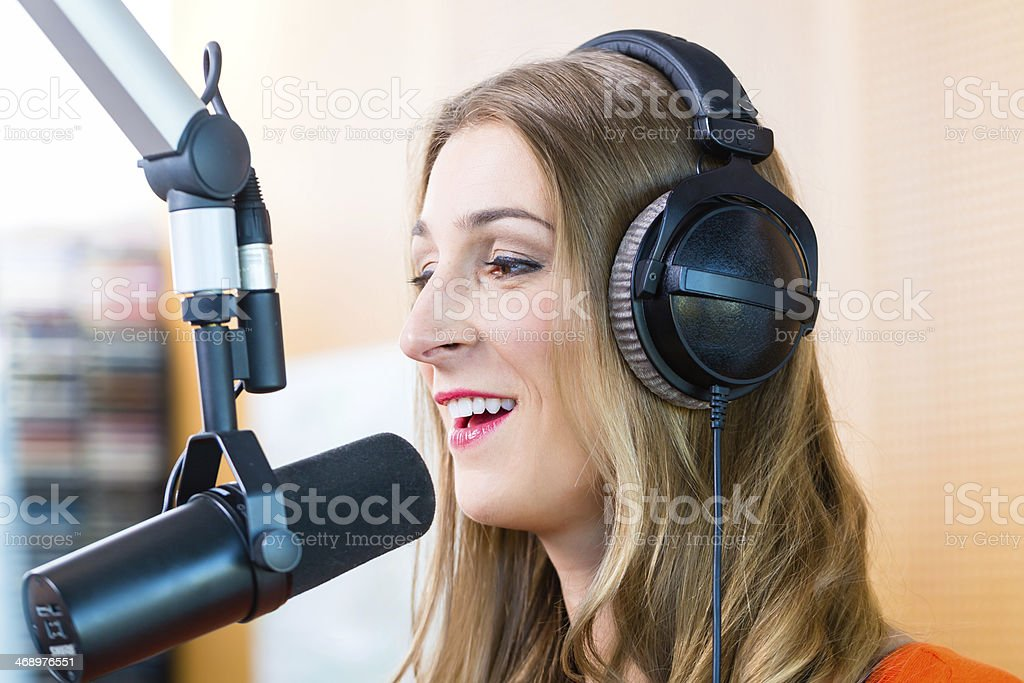 Female dj wearing headphone in front of microphone stock photo