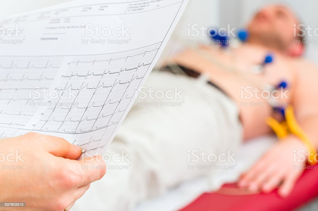 Female doctor analyzing ECG of patient stock photo