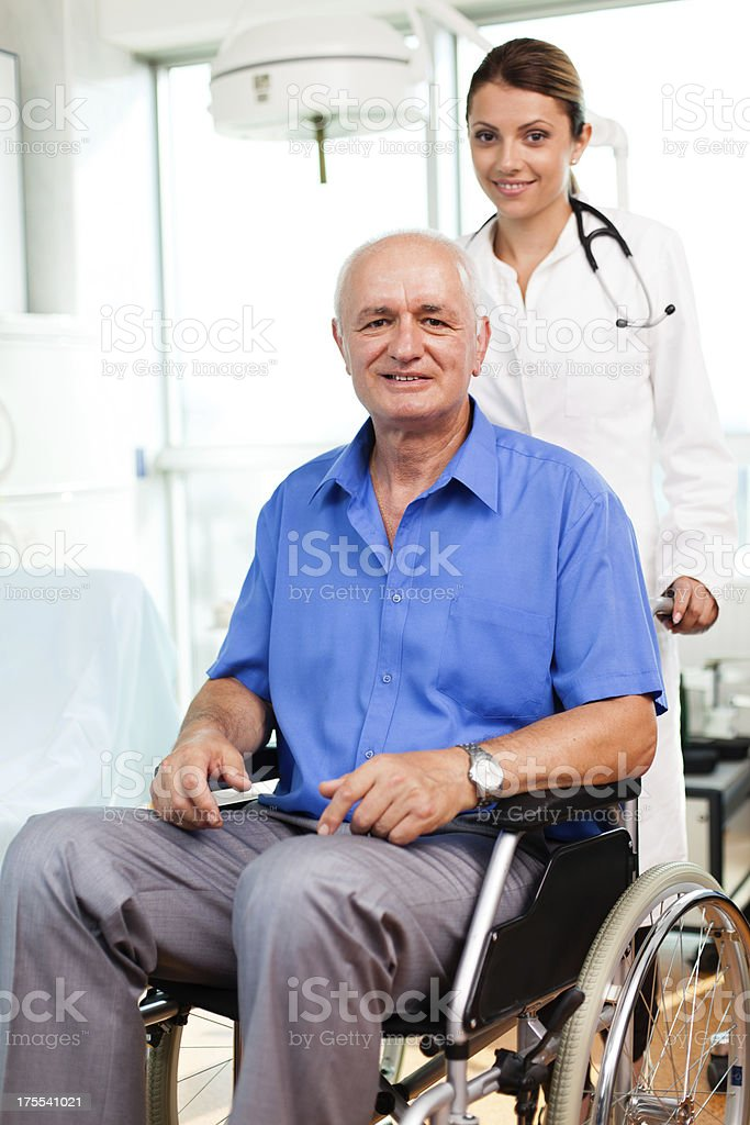 Female doctor assisting senior man in a wheelchair royalty-free stock photo