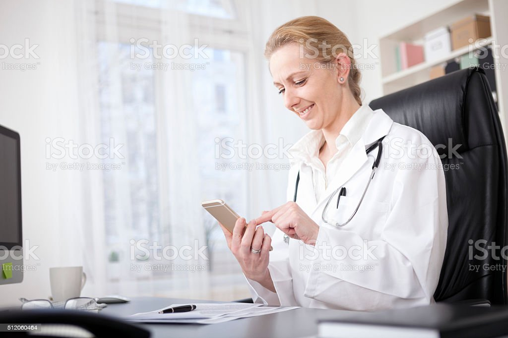 Female Doctor at her Table Browsing on her Phone stock photo