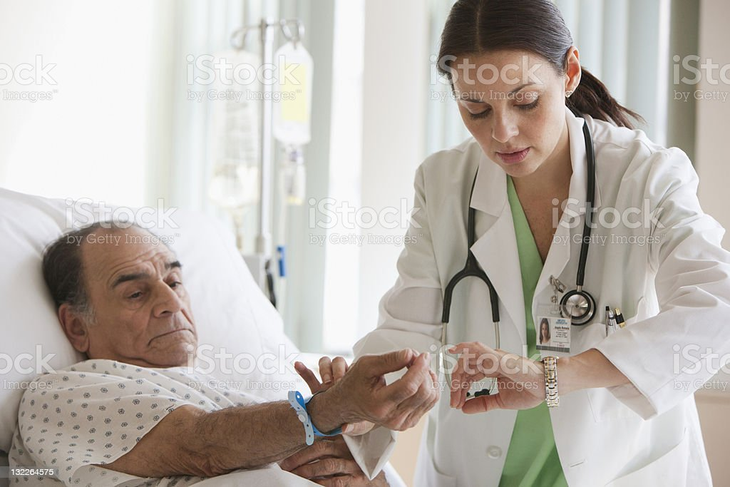 Female Doctor checking patient's pulse rate stock photo