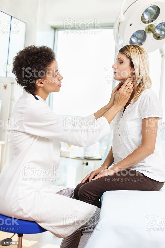 Female doctor checking thyroid gland stock photo