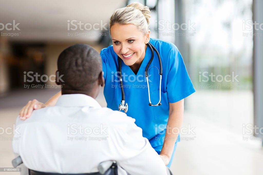 female doctor comforting disabled patient stock photo