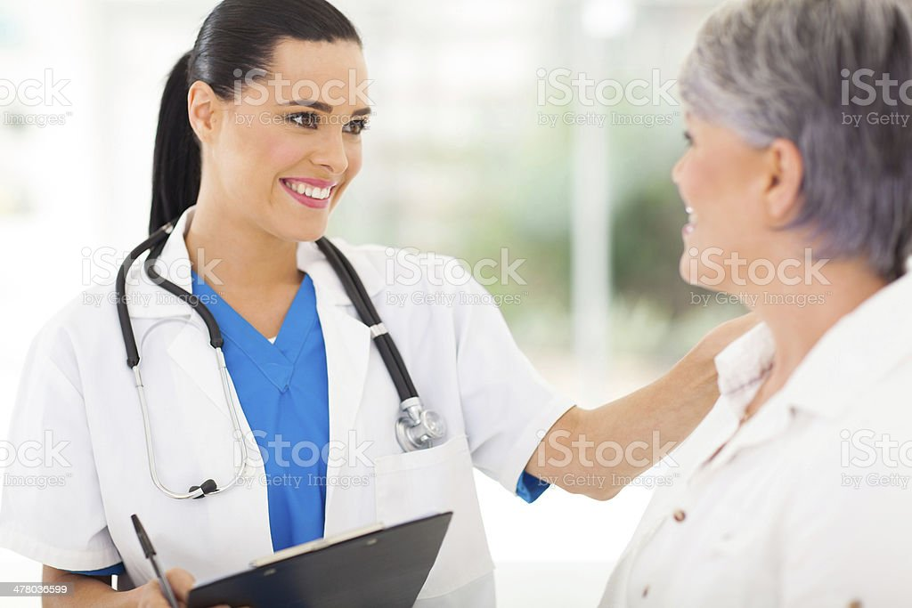 female doctor comforting middle aged patient stock photo