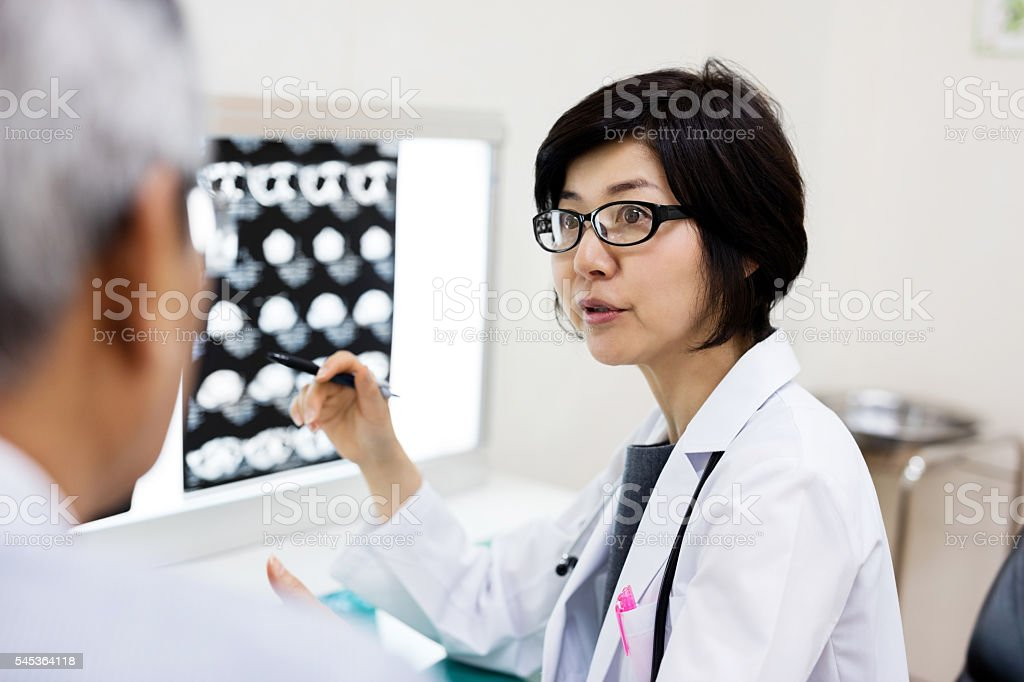 Female doctor discussing with man over MRIs in hospital stock photo