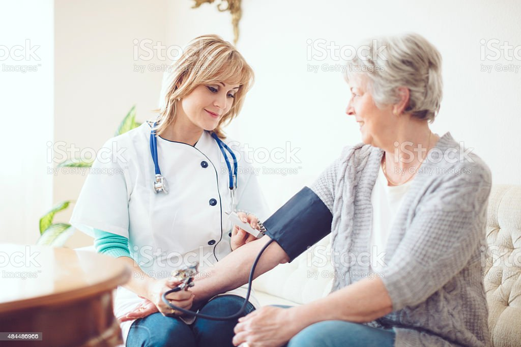 Female doctor examines her senior patient at home stock photo