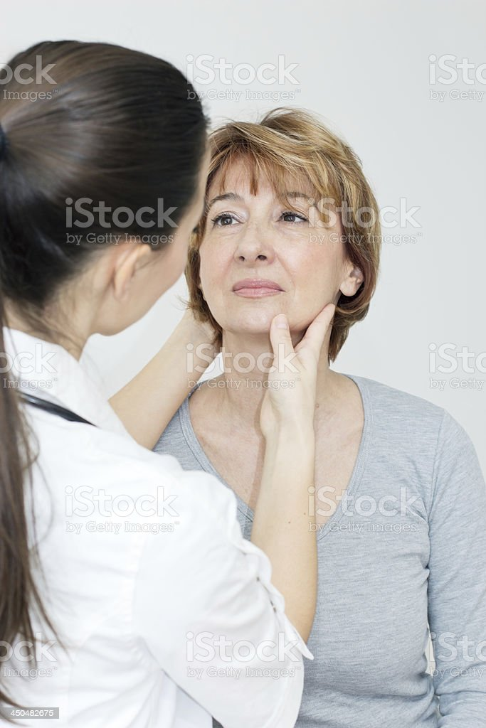 A female doctor examining a neck injury stock photo