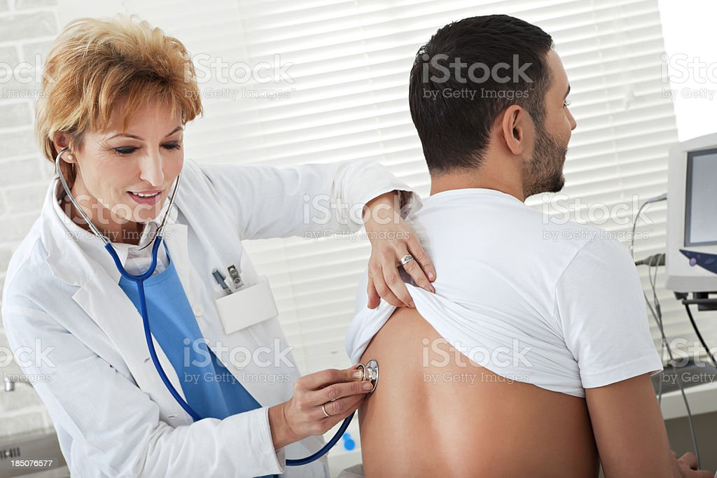 Female doctor examining a young man royalty-free stock photo